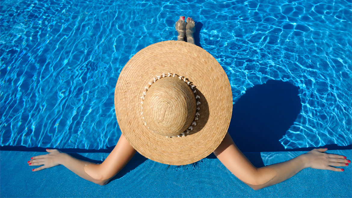 Woman sitting in pool with hat