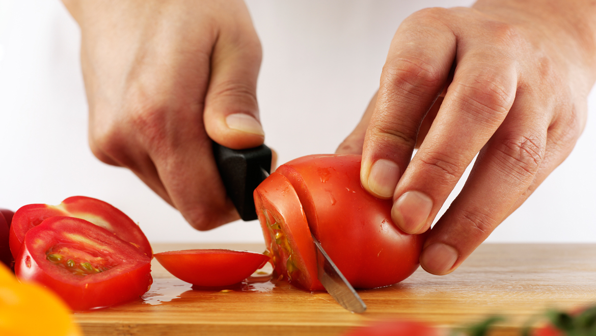 Chef cutting tomatoes