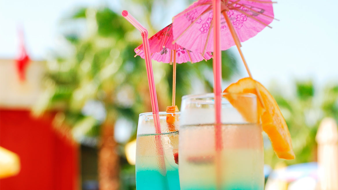 Cocktails with umbrellas and straws