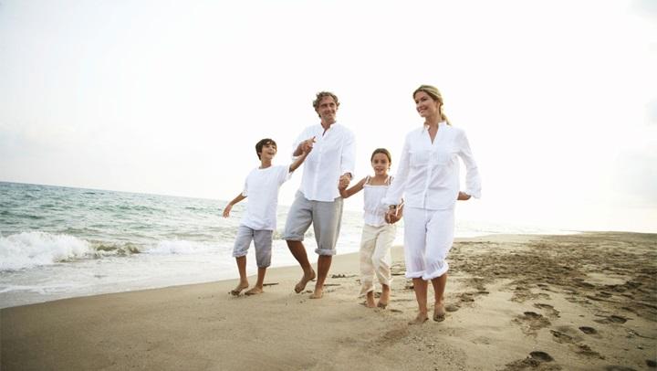 Family in white walking on beach