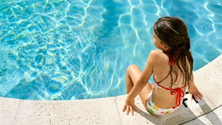 Girl sitting by pool