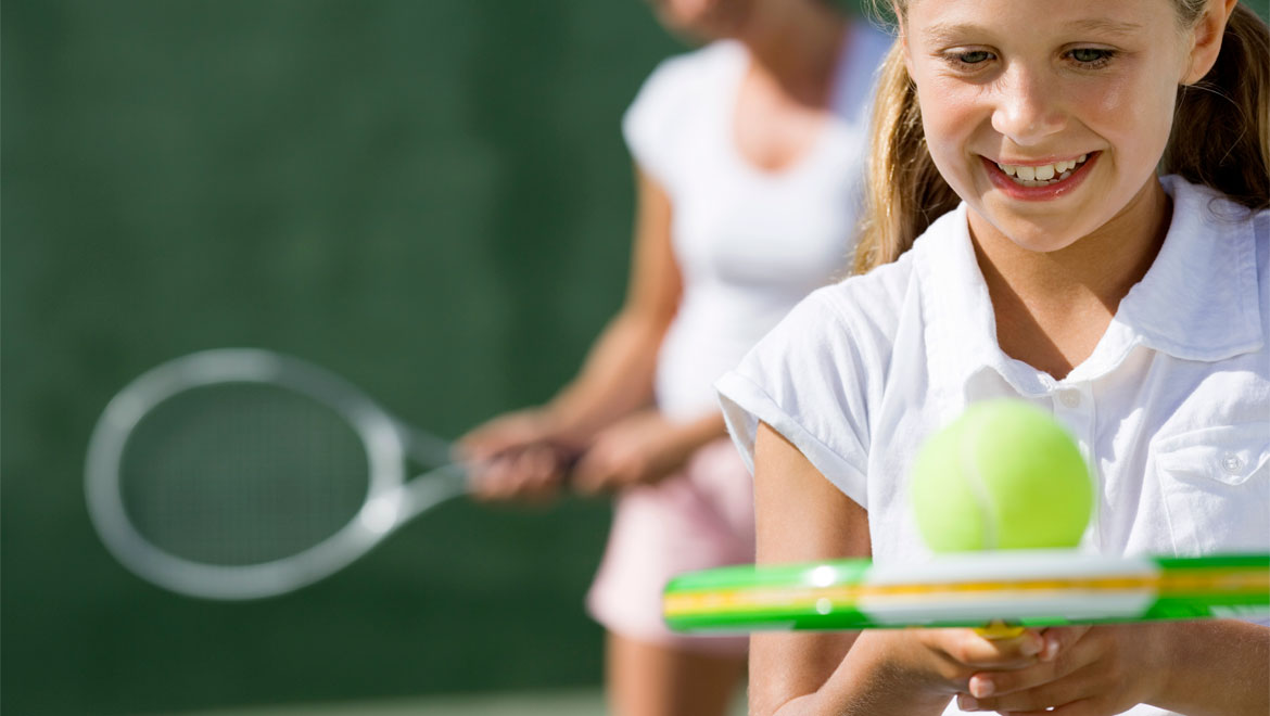 Girl with tennis ball and mother in background