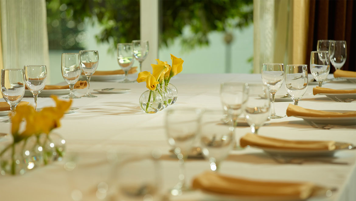Table setting with glasses and yellow flowers