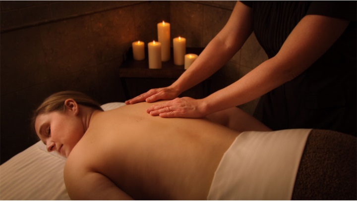 Massage with candles in background