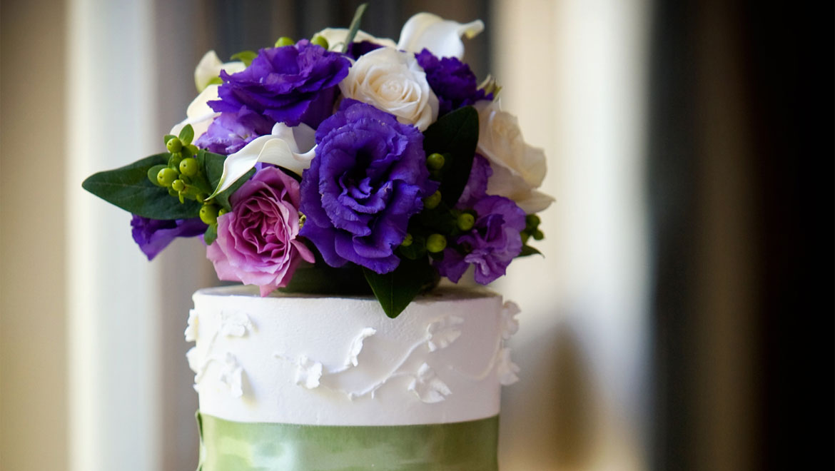 Purple flowers on top of wedding cake