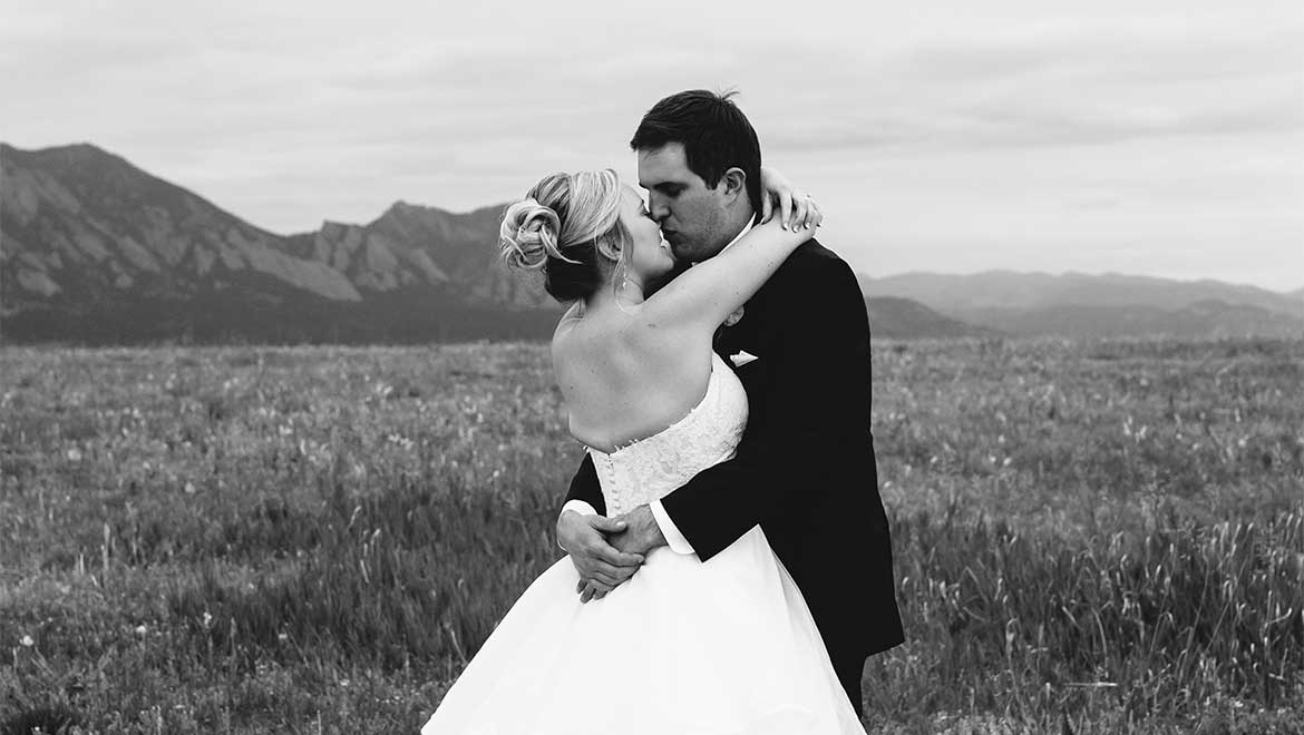Bride and groom kiss with mountains in background