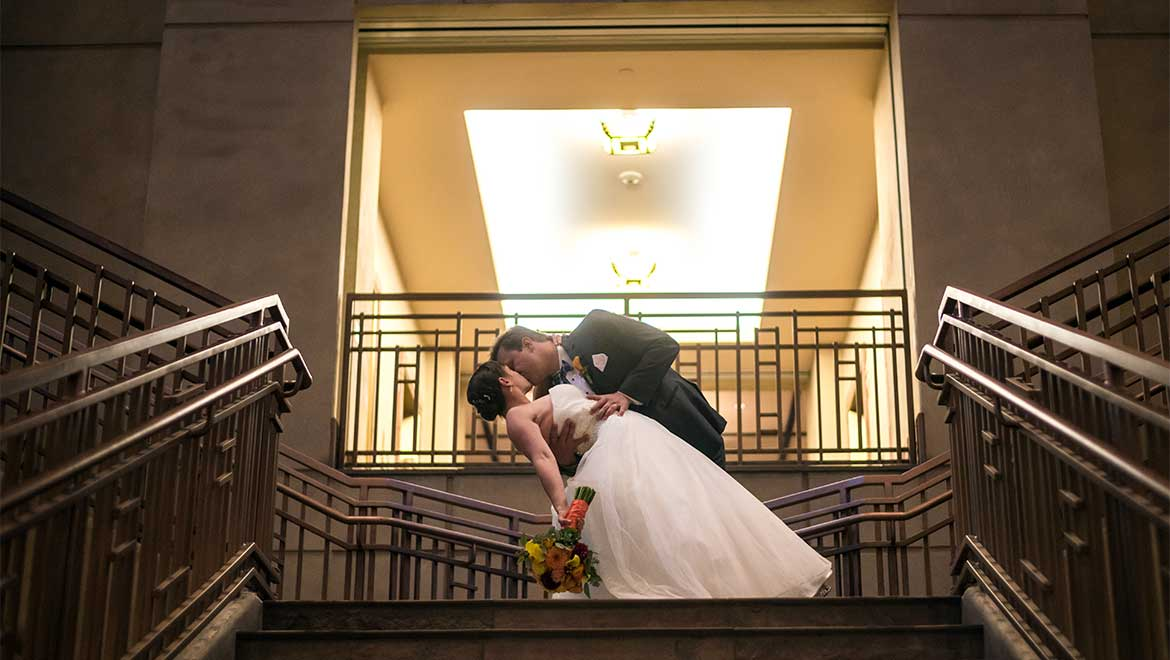 Bride and groom kiss at top of staircase