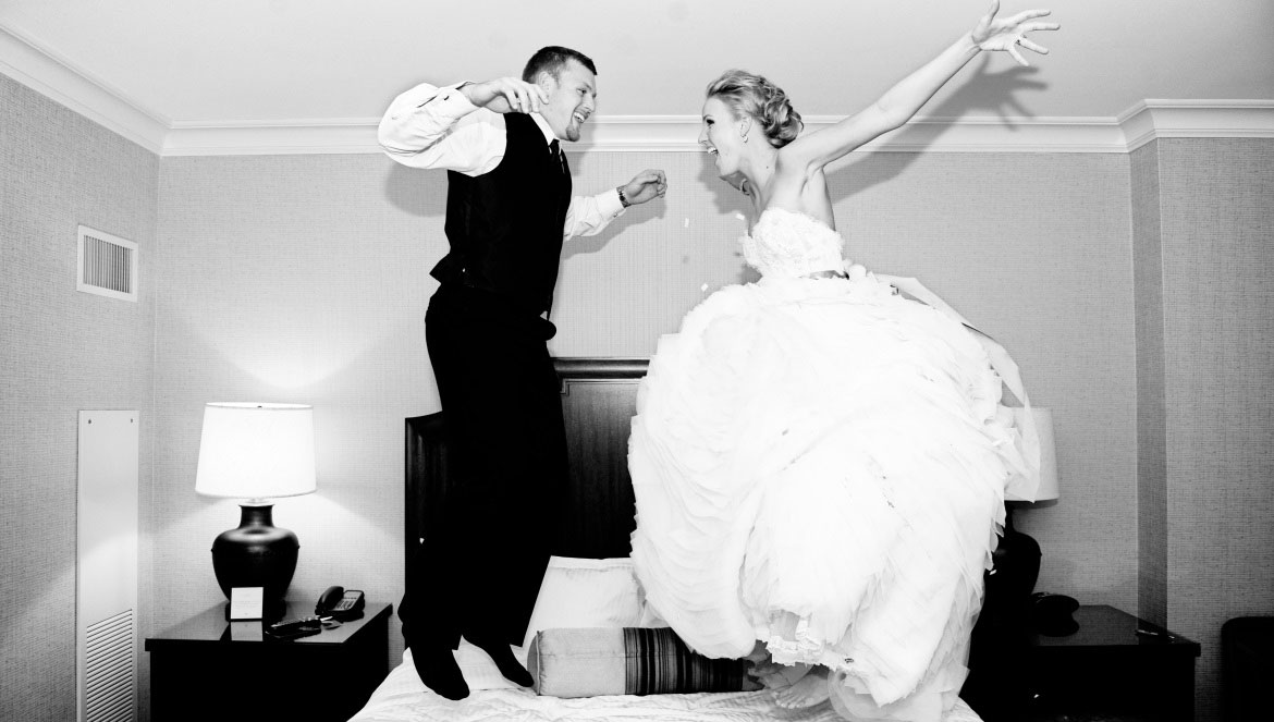 Bride and groom jumping on the bed