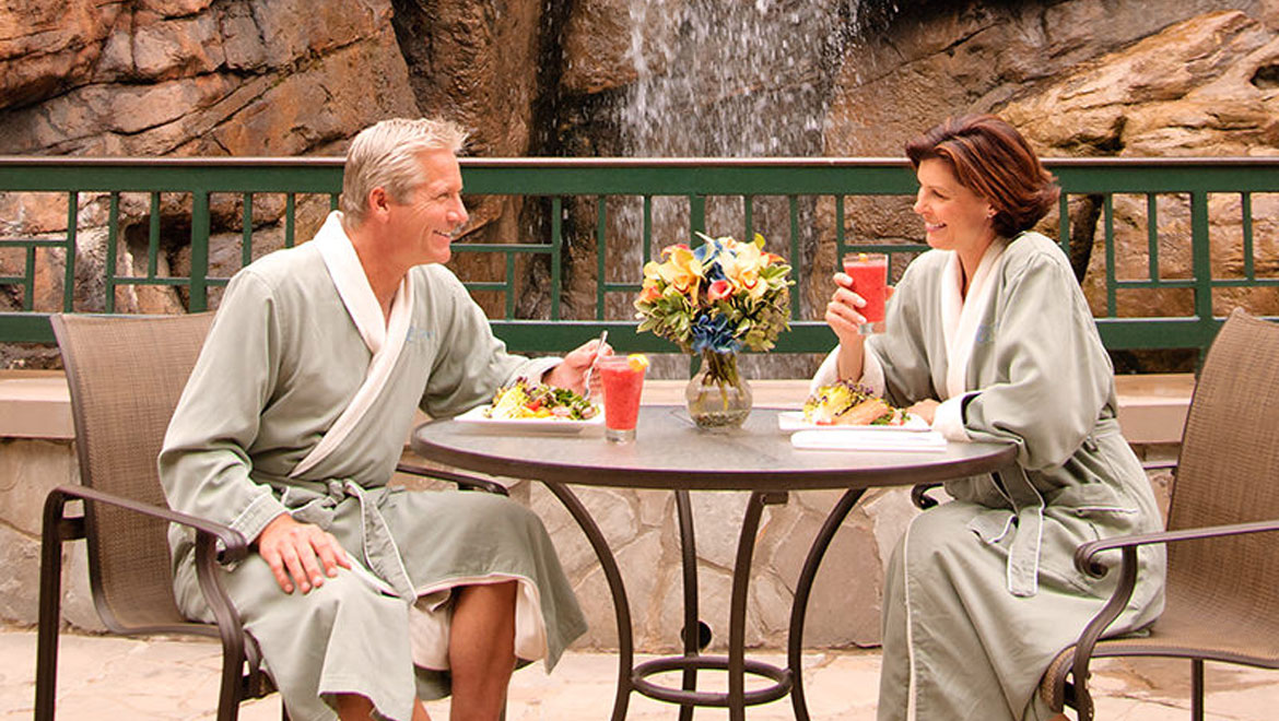 Couple in robes sitting outside Grove Park Inn spa