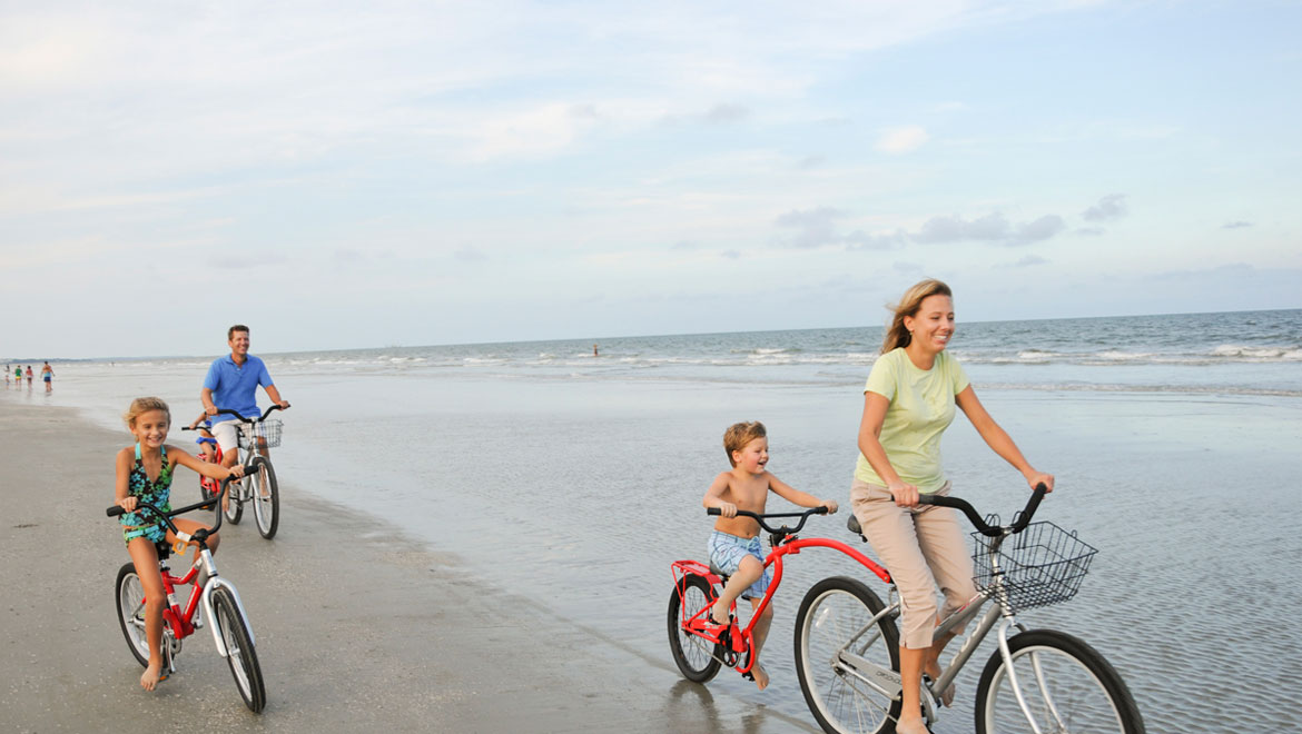 Family riding bikes on the sugar sand beaches of Hilton Head Island