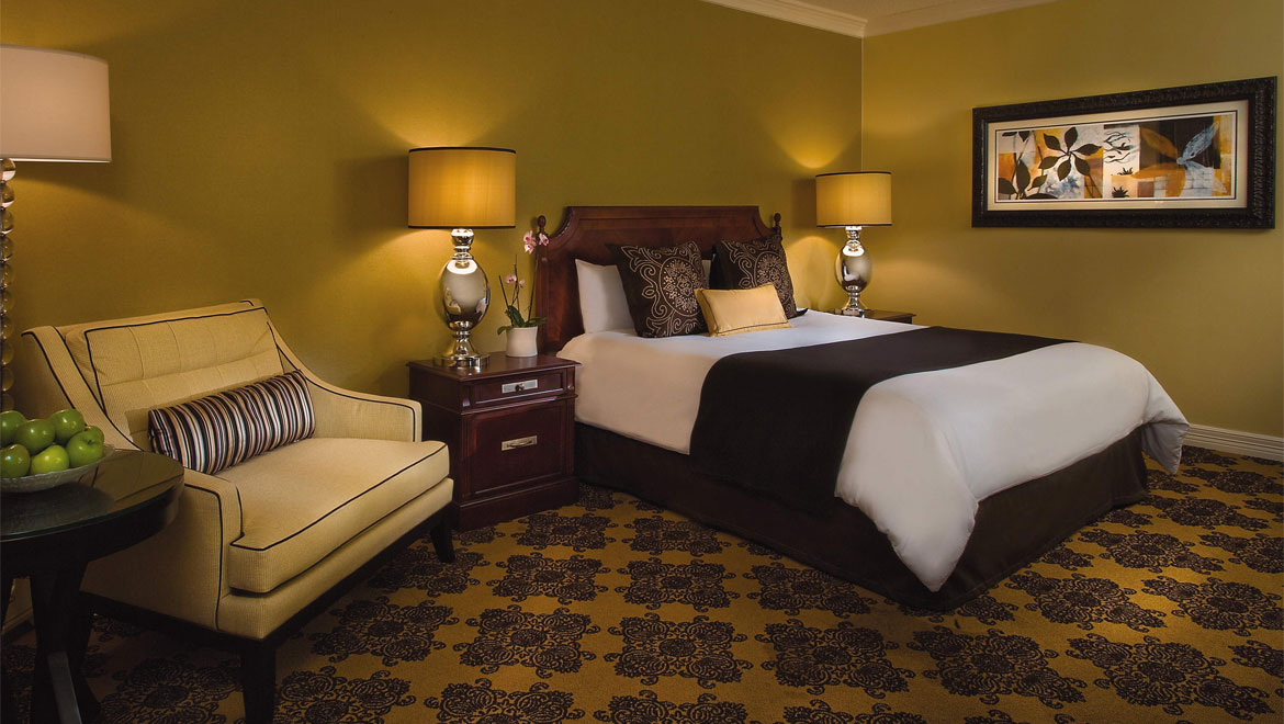 Guestroom bed and seating at Houston hotel