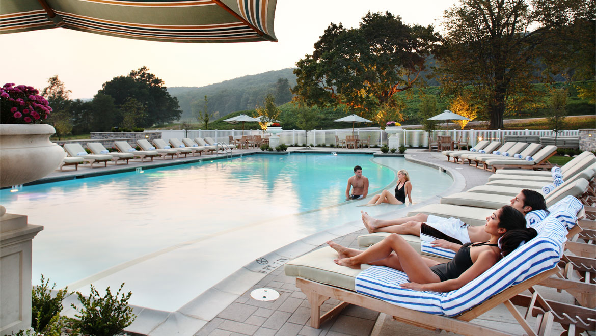 Guests lounging by outdoor pool at Bedford Springs