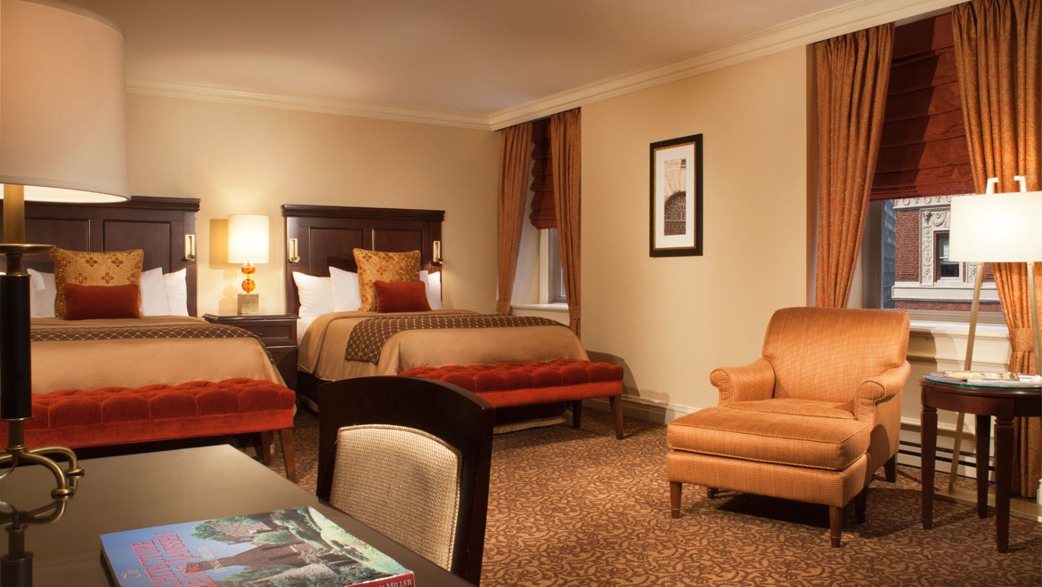 Photo of deluxe guest room: Classic room with two queen-size beds, a desk and desk chair, an armchair and side table.
