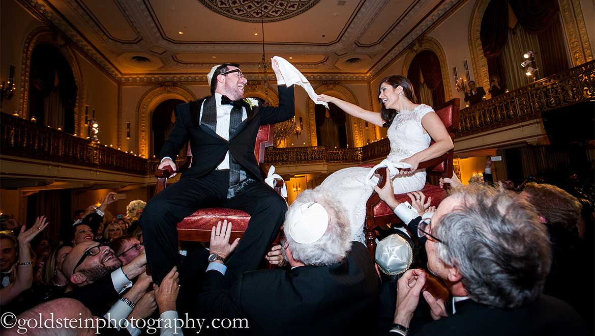 Bride and groom on chairs during The Hora