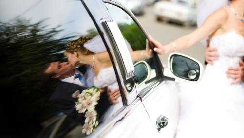 Bride and groom kiss outside of limo