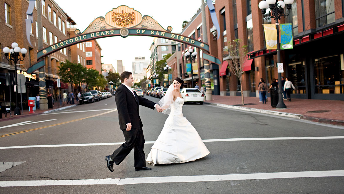Bride and groom in front of arch at San Diego hotel