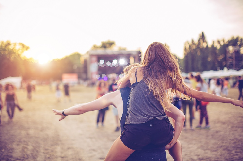 woman piggyback riding at music festival
