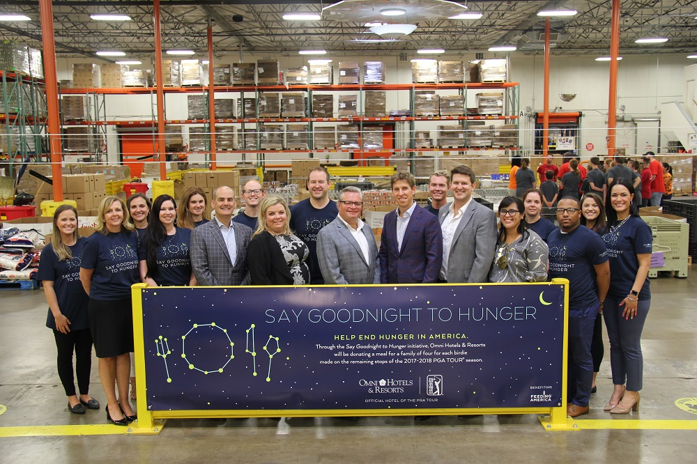 People standing behind sign in food bank