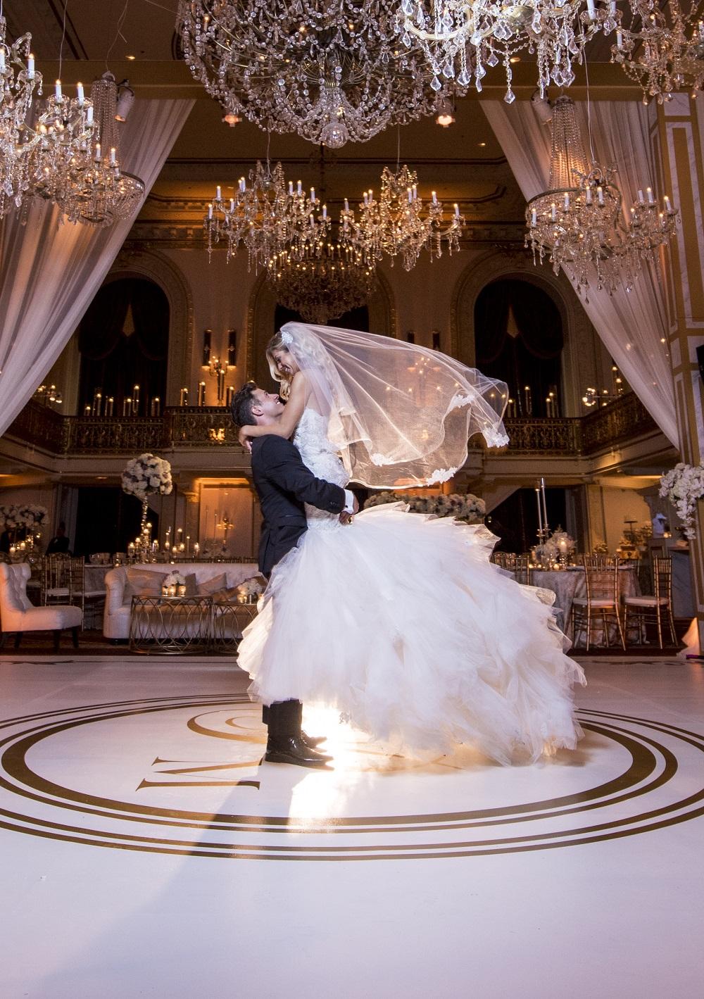 Groom carrying bride in ballroom
