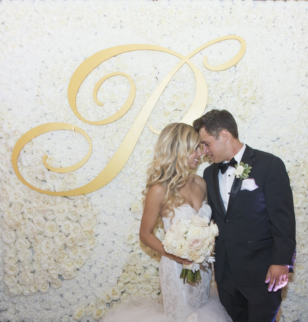 bride and groom in front of flower wall