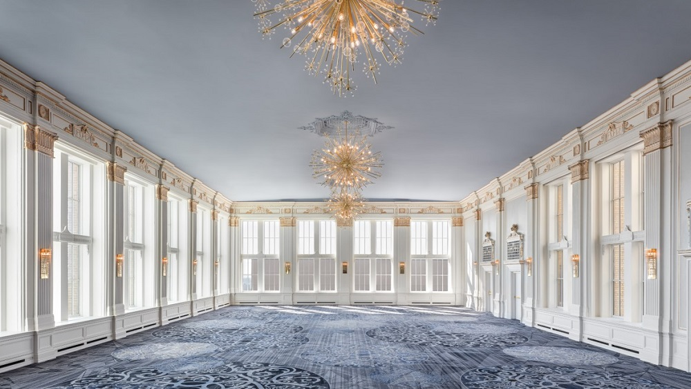 large ballroom with windows and three chandeliers