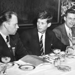 John F. Kennedy and two men at a table