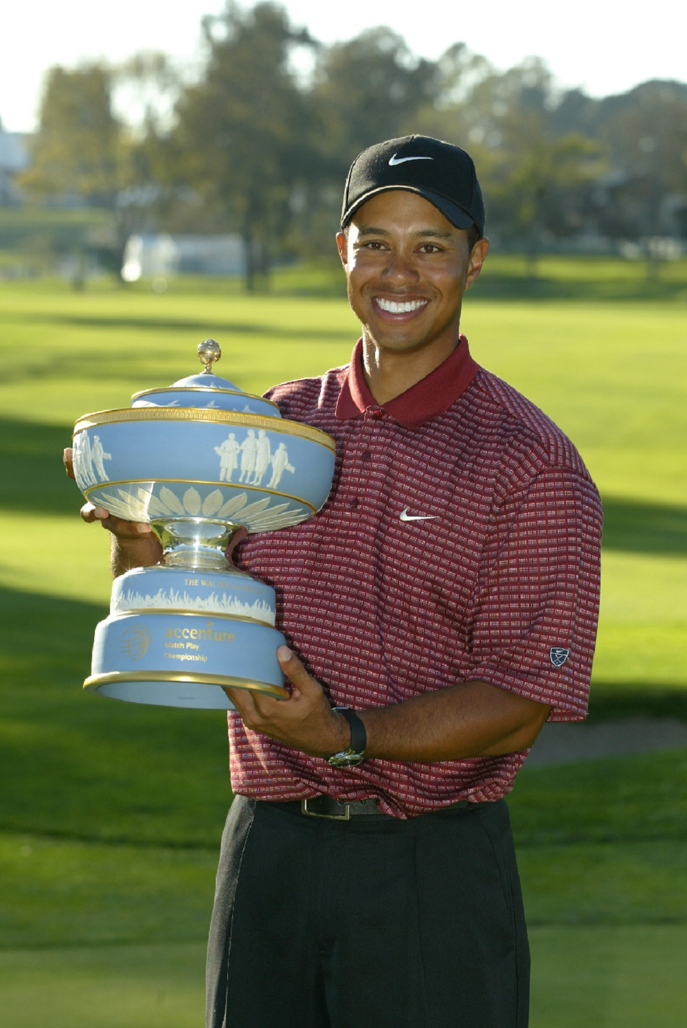 Tiger Woods holding trophy on golf course