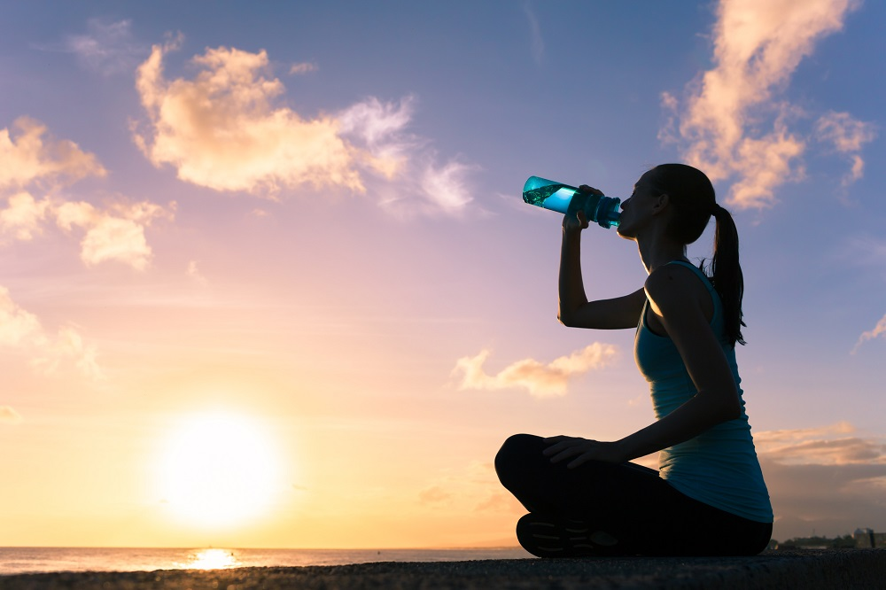 Woman drinking water at the beach