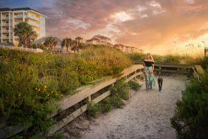 Woman walking dog on the beach in Amelia Island